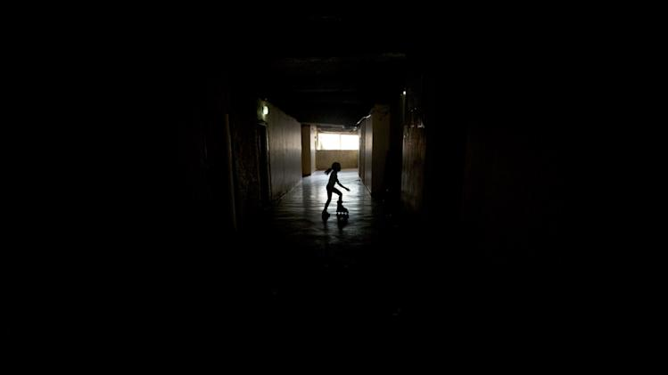 A girl skates in the abandoned halls inside the the world's tallest slum, the Tower of David, a half-built skyscraper that was abandoned in the 1990s and was transformed by squaters into a vertical ghetto, in Caracas, Venezuela, Tuesday, July 22, 2014. Officials and armed soldiers began moving out the first of thousands of squatters who have lived for nearly a decade in a soaring, half-built skyscraper in the heart of Caracas. (AP Photo/Fernando Llano)