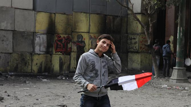 An Egyptian protester displays the national colors as skirmishes break out between demonstrators and security forces, unseen, near Tahrir Square, Cairo, Egypt, Friday, Jan. 25, 2013. Egyptian opposition protesters are gathering in Cairo's Tahrir Square to mark the second anniversary of the uprising that toppled Hosni Mubarak's autocratic regime. (AP Photo/Thomas Hartwell)