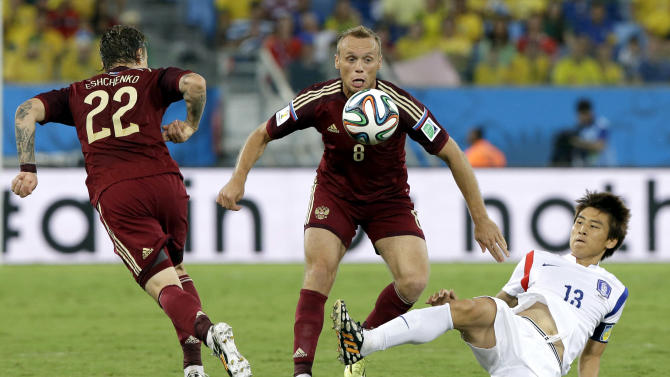 Russia's Andrei Yeshchenko, left, and Russia's Denis Glushakov challenge South Korea's Koo Ja-cheol during the group H World Cup soccer match between Russia and South Korea at the Arena Pantanal in Cuiaba, Brazil, Tuesday, June 17, 2014. (AP Photo/Lee Jin-man)