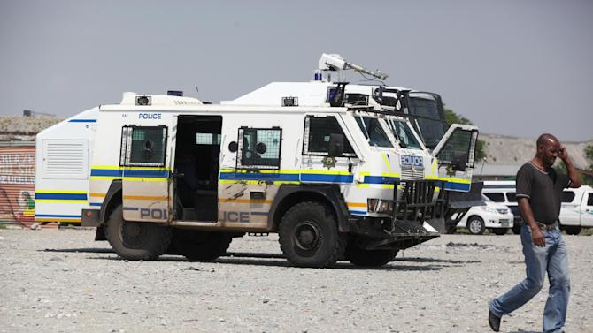 A man walks by a police vehicle stationed by a meeting of striking miners near Rustenburg, South Africa, on Wednesday, Nov. 14, 2012. Workers discussed a possible deal with Anglo American Platinum, or Amplats, on Wednesday as their weeks-long strike continued. Amplats is the world's top producer of platinum. (AP Photo/Jon Gambrell)