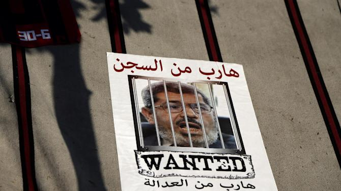 "A poster of Egypt's President Mohammed Morsi seen on a tent during a demonstration in front of the Ministry of Defense, in Cairo, Egypt, Wednesday, June 26, 2013. In abstract terms, protests planned for Sunday, June 30, 2013 aiming to force out Egypt's Islamist president violate a basic principle of democracy: If an election has been held, all must respect the results, otherwise it's political chaos. Supporters of President Mohammed Morsi have been angrily making that argument for days. Those behind the protests insist he lost the legitimacy of that election victory by power grabs and missteps. Arabic at the poster reads, "" Fugitive from Justice, Fugitive from prison"". (AP Photo/Hassan Ammar)"