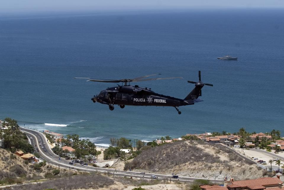 A Mexican federal police helicopter flies as a Mexican navy ships patrols the bay waters in San Jose del Cabo in Mexico's Baja Peninsula, Friday, June 15, 2012. Security has been beefed up in preparation for the upcoming G-20 summit that will be held in Los Cabos June 18-19. (AP Photo/Fernando Castillo)