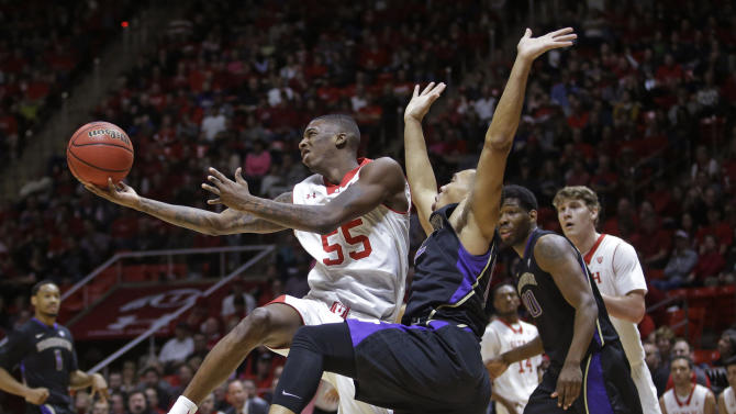 Utah guard Delon Wright (55) flips the ball up as Washington guard Andrew Andrews, center, defends in the second half during an NCAA college basketball game Sunday, Jan. 25, 2015, in Salt Lake City. Utah won 77-56. (AP Photo/Rick Bowmer)