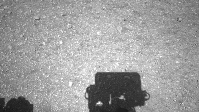 This image released by NASA on Wednesday, Aug. 8, 2012, shows the edge of NASA's Curiosity rover, showing the shadow of the rover's now-upright mast in the center, and the arm's shadow at left. The navigation camera is used to help find the sun -- information that is needed for locating, and communicating, with Earth. (AP Photo/NASA)
