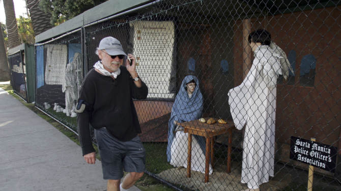 """FILE - In this Dec. 13, 2011 file photo, a man walks past two of the traditional Nativity scenes along Ocean Avenue at Palisades Park in Santa Monica, Calif. Avowed atheist Damon Vix last year won two-thirds of the booths in the annual, city-sponsored lottery to divvy up spaces in the live-sized Nativity display.  But he only put up one thing: A sign that read """"Religions are all alike - founded on fables and mythologies."""" Vix left the rest of his allotted spaces empty, and in so doing, upended a Christmas tradition that began in Santa Monica nearly 60 years ago. (AP Photo/Ringo H.W. Chiu, file)"""