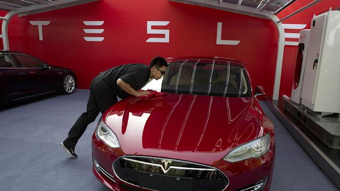 FILE - In this April 22, 2014 file photo, a worker cleans a Tesla Model S sedan before a event to deliver the first set of cars to customers in Beijing. Tesla Motors Inc. reports quarterly financial results on Thursday, July 31, 2014. (AP Photo/Ng Han Guan, File)