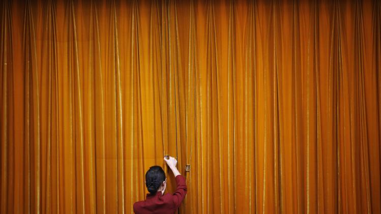 An attendant puts clamps on a curtain inside the Great Hall of the People during the closing ceremony of the Chinese People's Political Consultative Conference (CPPCC) in Beijing