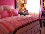 Use magenta instead of pink, stripes instead of flowers and a rough looking bed--and your pink bedroom won't seem too girly.