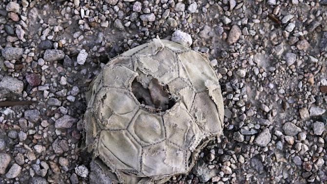 In this Sept. 25, 2012 photo, a deflated soccer ball lays in a street in an area that used to be the town where miners lived at the Chuquicamata copper mine in Atacama desert in northern Chile. The town was moved as the mine grew.  Experts say that by 2019 the Chuquicamata copper mine will be unprofitable, so state-owned mining company Codelco is trying to head off closure by converting the open pit into the world's largest underground mine. Codelco believes the mine still has much more to give, with reserves equal to about 60 percent of all the copper exploited in the mine's history still buried deep beneath the crater. (AP Photo/Jorge Saenz)
