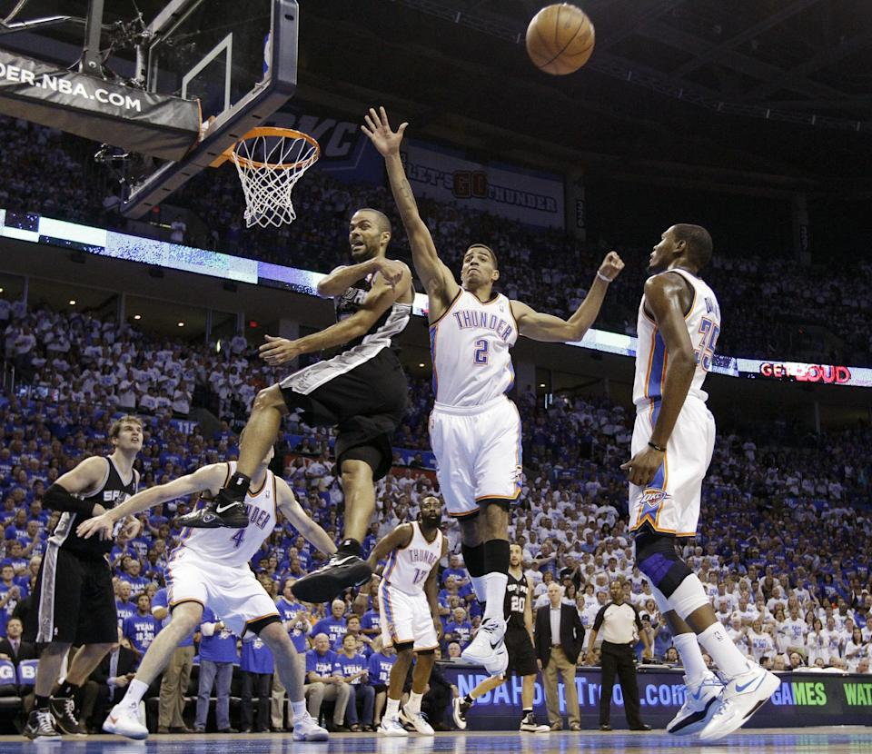 San Antonio Spurs guard Tony Parker (9), of France, passes the ball as Oklahoma City Thunder guard Thabo Sefolosha (2), of Switzerland, defends during the first half of Game 4 in the NBA basketball playoffs Western Conference finals, Saturday, June 2, 2012, in Oklahoma City. (AP Photo/Eric Gay)