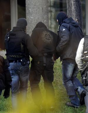 German suspected far-right activist identified only as  Andre E. , center,  is led  to the federal court in Karlsruhe, Germany,Thursday Nov. 24,  2011. German prosecutors say police have arrested the  man on charges he supported a neo-Nazi terror group that is believed to have killed 10 people and carried out several attacks over more than a decade.  The Federal Prosecutors' Office said in a statement Thursday that a police special operations team arrested the 32-year-old German citizen near Berlin in a morning raid.  (AP Photo/dapd/Ronald Wittek)