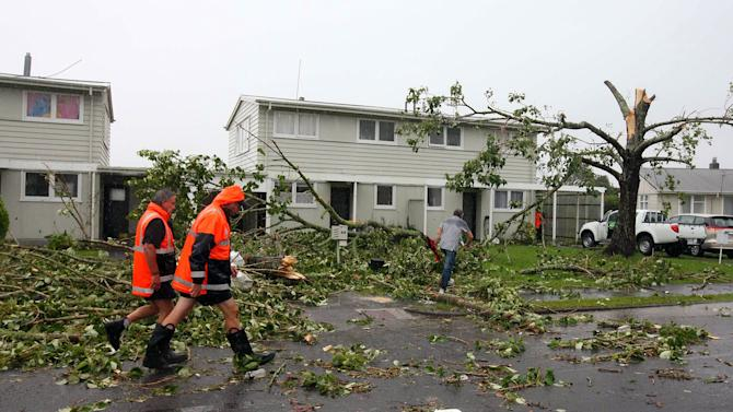 Emergency workers walk through debris in Auckland, New Zealand, following a tornado Thursday, Dec. 6, 2012. A small tornado ripped through the city, leaving at least three people dead. (AP Photo/New Zealand Herald, Chris Gorman) AUSTRALIA OUT, NEW ZEALAND OUT