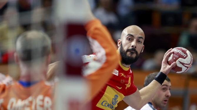 Rocas of Spain challenges goalkeeper Omeyer of France during their semi-final match of the 24th Men's Handball World Championship in Doha