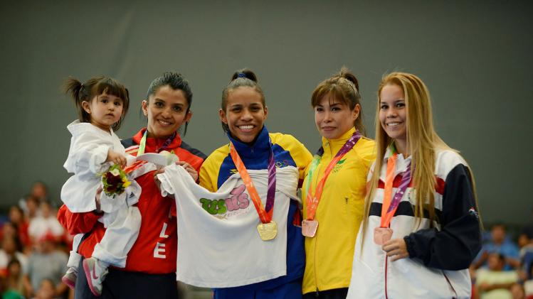 Gold medallist Genesis Navarrete poses for the media with silver and bronze medallist during the awards ceremony of women's karate -55 kg category competition at the ODESUR in Santiago