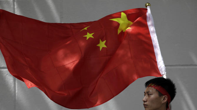 One of Chinese protesters holds a Chinese flag in front of the Japanese Consulate General during an anti-Japan rally in Shanghai, China, Saturday Sept. 15, 2012. Tensions between the two countries flared anew after the Japanese government bought the disputed islands from their private Japanese owners this week. The uninhabited islands, Senkaku in Japan and Diaoyu in China, claimed by both countries as well as Taiwan, have become a rallying point for nationalists on both sides. (AP Photo/Eugene Hoshiko)