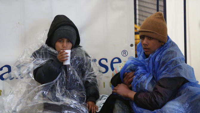 Children try to keep themselves warm as migrants and refugees wait to continue their train journey to western Europe at a refugee transit camp in Slavonski Brod