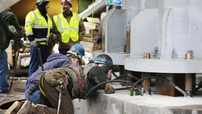 Ironworkers align the first piece of the spire for One World Trade Center as it is lowered by construction cranes into position on the roof of the tower, Tuesday, Jan. 15, 2013 in New York. When the spire is completed the building will top off at 1776 feet (541 meters), making it the tallest building in North America. (AP Photo/Mark Lennihan)
