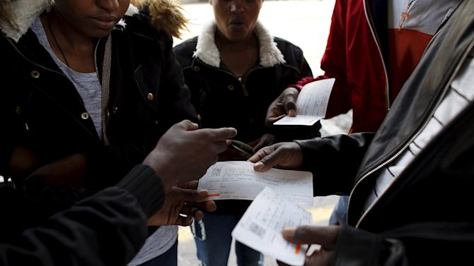 Migrants check their train tickets to Germany, as they wait to take a train for the Italian border at Bolzano railway station