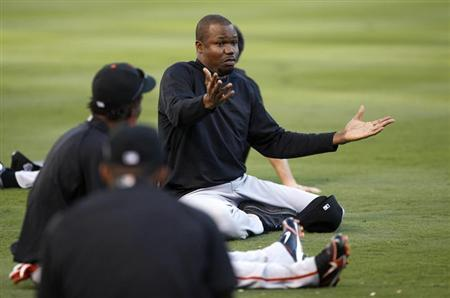 San Francisco Giants Guillermo Mota talks with teammates while he stretches during workouts ahead of Game 3 of Major League Baseball's World Series in Arlington, Texas.