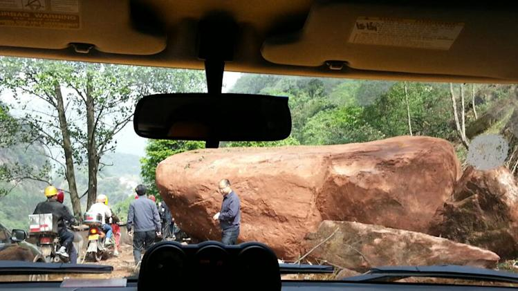 In this photo provided by China's official Xinhua News Agency, a giant rock blocks the road, about 20 kilometers (12.5 miles)  from the county seat of Lushan in Ya'an city, southwest China's Sichuan Province, Saturday, April 20, 2013. A powerful earthquake jolted China's Sichuan province Saturday near where a devastating quake struck five years ago.  (AP Photo/Xinhua, Hai Mingwei) NO SALES