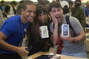 Customers and Apple employee pose with new Apple iPhone 5s phones at the Apple Retail Store in Manhattan, New York