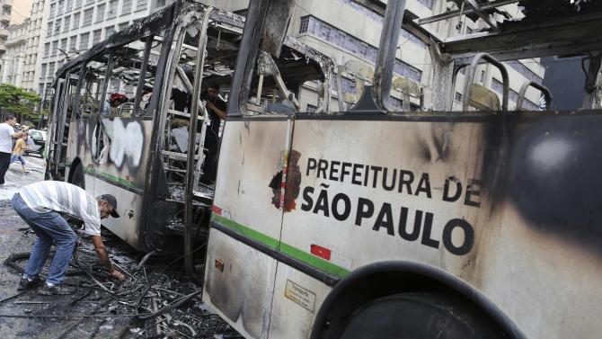 A man scavenges for pieces of iron from a burnt-out bus along a street, after riot police clashed with members of Brazil's Movimento dos Sem-Teto in downtown Sao Paulo