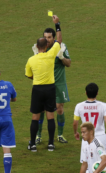 Italy's Gianluigi Buffon is booked by referee Diego Alba from Argentina as Japan's Keisuke Honda, bottom right, prepares for the penalty during the soccer Confederations Cup group A match between Ital