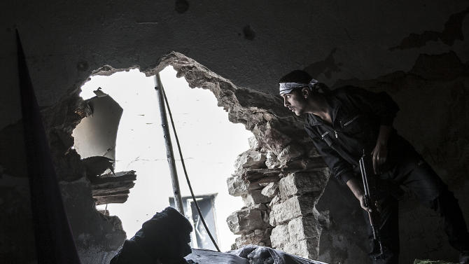 In this Wednesday, Oct. 24, 2012 photo, a Free Syrian Army fighter watches over an enemy position as rebel fighters belonging to the Liwa Al Tawhid group carry out a military operation at the Moaskar front line, one of the battlefields in the Karmal Jabl neighborhood, in Aleppo, Syria. (AP Photo/Narciso Contreras)