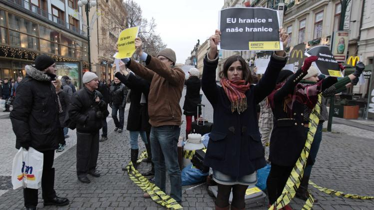 Pedestrians look at Amnesty International activists holding signs during a protest in Prague