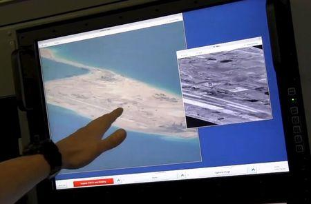 Still image from United States Navy video shows a U.S. Navy crewman aboard a surveillance aircraft pointing to a computer screen purportedly showing Chinese construction on the reclaimed land of Fiery Cross Reef in the disputed Spratly Islands