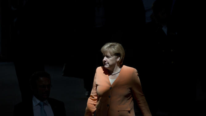 German Chancellor Angela Merkel walks through a beam of sunlight as she arrives for a special session of the Germany Parliament Bundestag in Berlin, Germany, Thursday, July 19, 2012. Germany's Parliament is interrupting its summer break to vote on a rescue package worth up to euro 100 billion (US dollar 122 billion) for Spain's ailing banks. (AP Photo/Gero Breloer)