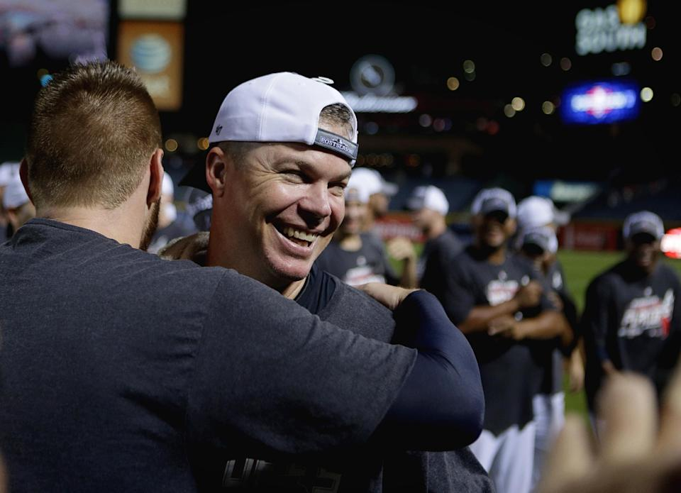 Atlanta Braves' Chipper Jones, facing camera, is embraced by teammate Freddie Freeman after the Braves beat the Miami Marlins 4-3 in a baseball game, clinching at least an NL wild-card berth Tuesday, Sept. 25, 2012, in Atlanta. (AP Photo/David Goldman)