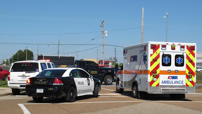 Police vehicles and an ambulance block a road near a Tennessee National Guard armory where two Guard members were shot on Thursday, Oct. 24, 2013, in Millington, Tenn. A member of the National Guard opened fire at the armory outside a U.S. Navy base in Tennessee, wounding two soldiers before being subdued and disarmed by others soldiers, officials said Thursday. (AP Photo/Adrian Sainz)