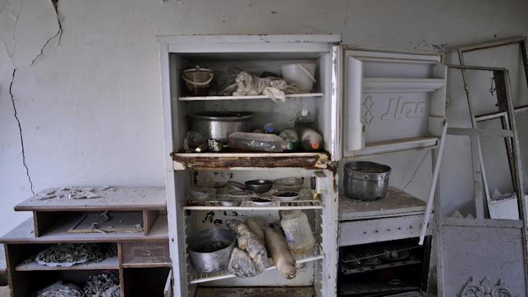 In this Friday, Aug. 31, 2012 photo, food remains in the damaged kitchen of a Syrian house, one of more than a dozen homes destroyed in a Syrian government airstrike on August 15, 2012, that killed more than 40 people, in Azaz, on the outskirts of Aleppo, Syria.  Over the past week, survivors and relatives have returned daily to collect from the rubble what can be salvaged as they also relive the day of the airstrike. (AP Photo/Muhammed Muheisen)