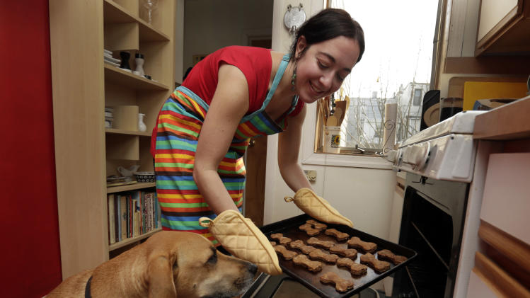 "In this Saturday, Dec. 15, 2012 photo, New York pet columnist for the magazine ""Everyday with Rachael Ray,"" Sarah Zorn and her dog Rowdy pose for photos with her gingerbread holiday dog biscuits, in her home in Brooklyn, N.Y. The holidays might be the easiest time of the year to cook for dogs because human menus can be so easily adapted to their needs, said Zorn. (AP Photo/Richard Drew)"