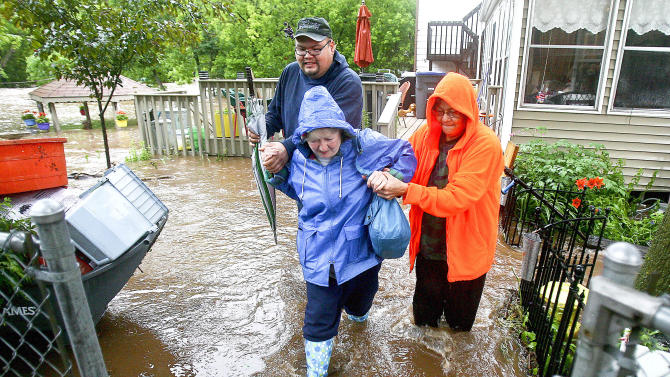 Carl Carlson III, left, and Connie Strong, right, help evacuate Jan Martin from her home in the Lincoln Park neighborhood after record rainfall hit the Duluth, Minn., area Wednesday June, 20, 2012. Most areas received seven to 10 inches of rain in the past 24 hours. Martin remarked that she has lived in the neighborhood for 69 years and has never seen Miller Creek this high. (AP Photo/The Duluth News-Tribune, Clint Austin)