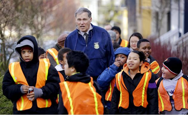"Gov. Jay Inslee, center, escorts elementary school students on a ""walking school bus"" Tuesday morning, March 11, 2014, in Seattle. Inslee joined about two dozen students on their way to clas"