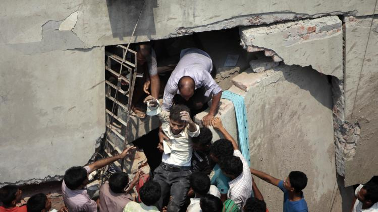 A man who was trapped in an collapsed eight-story building housing several garment factories is reccued in Savar, near Dhaka, Bangladesh, Wednesday, April 24, 2013. Dozens were killed and many more are feared trapped in the rubble. (AP Photo/ A.M. Ahad)