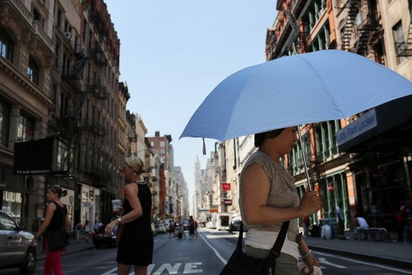 A woman walks down the street under a sun umbrella during warm weather on July 6, 2012 in New york City. Forecasts for tomorrow are predicting temperatures near 100 degrees Fahrenheit (38 Celsius) and