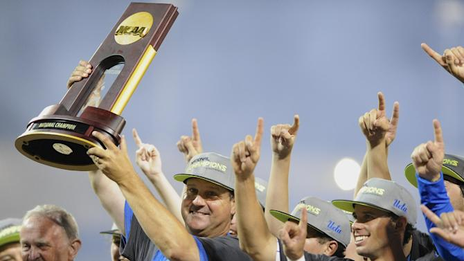 UCLA coach John Savage is surrounded by players as he hoists the trophy after beating Mississippi State 8-0 in Game 2 of the NCAA College World Series baseball finals, Tuesday, June 25, 2013, in Omaha, Neb., winning the championship. (AP Photo/Eric Francis)