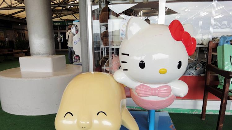 This Sept. 5, 2012 photo shows a Hello, Kitty children's ride next to a ride depicting a dugong at the Toba Aquarium in Toba, Japan. Dugongs, a sea mammal related to the manatee, are rare in captivity but Toba has a real one on display named Serena. (AP Photo/Linda Lombardi)