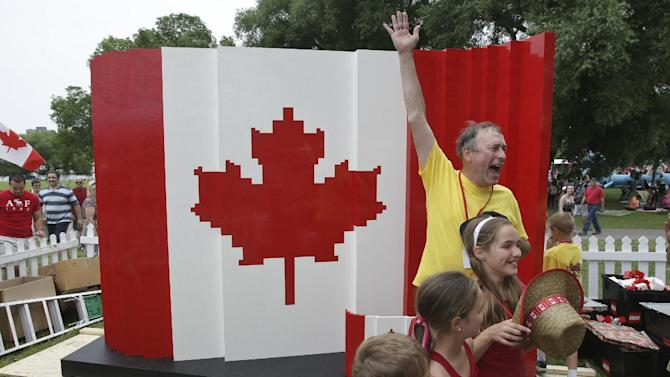 IMAGE DISTRIBUTED FOR LEGO SYSTEMS, INC - Master Model Builder Dan Steininger celebrates with kids after the last brick was laid on his piece during the Canada Day LEGO Flag Build, on Monday July 1, 2013 at Parc Jacques-Cartier Park in Gatineau, Quebec. For Canada Day, children could help build a Canadian flag made out of 128,000 LEGO bricks. (Francis Vachon / AP Images for LEGO Systems, Inc.)