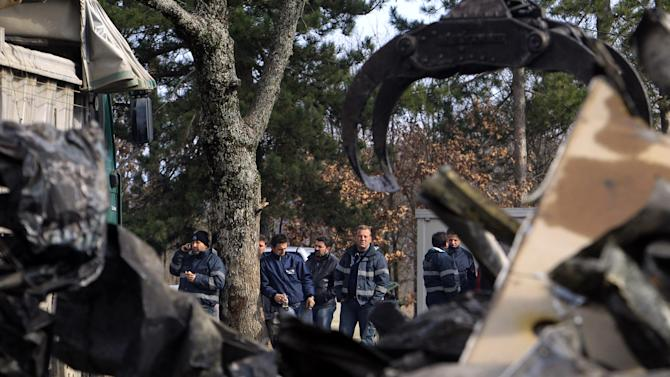 Employees  of Hellas Gold, are stand behind  a burnt van  at a mining facility  near the village of Skouries, located on the northern peninsula of Halkidiki Greece, on Sunday, Feb. 17 2013.  About 40 masked attackers raided the facilities of a prospective gold mine in northern Greece overnight Sunday, setting machinery and offices alight, authorities said. There has long been opposition to the prospect of a gold mine and processing plant being built at Skouries in the Halkidiki peninsula, with some residents objecting to what they say will be the destruction of the environment and of pristine forest in the area, leading to the loss of tourism and other local activities such as farming, the rearing of livestock and fishing. (AP Photo/Nikolas Giakoumidis)