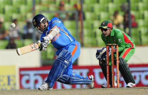 Sachin Tendulkar (left) plays a shot as the Bangladeshi captain Mushfiqur Rahim looks in Dhaka