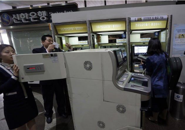 Two bank clerks, left, check an automated teller machine at a branch of Shinhan Bank after the bank's computer networks are fixed in Seoul, South Korea, Wednesday, March 20, 2013. Computers networks a