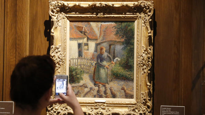 "In a Saturday, Feb. 8, 2014 photo, a visitor to the Fred Jones Jr. Museum of Art at the University of Oklahoma in Norman, Okla., takes a photograph of a piece called ""Shepherdess Bringing in Sheep"" by French impressionist artist Camille Pissarro at the museum. For more than a decade, the University of Oklahoma has exhibited ""Shepherdess Bringing in Sheep,"" bequeathed to it by the wife of an oil tycoon. But renewed claims by a family that owned the oil painting before World War II has drawn the school's fundraising arm into a fight it thought was settled in Switzerland more than 60 years ago. (AP Photo/Sue Ogrocki)"