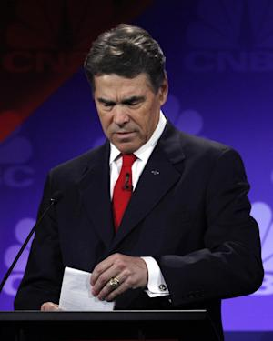 Republican presidential candidate Texas Gov. Rick Perry looks at his notes during a Republican Presidential Debate at Oakland University in Auburn Hills, Mich., Wednesday, Nov. 9, 2011.  (AP Photo/Paul Sancya)