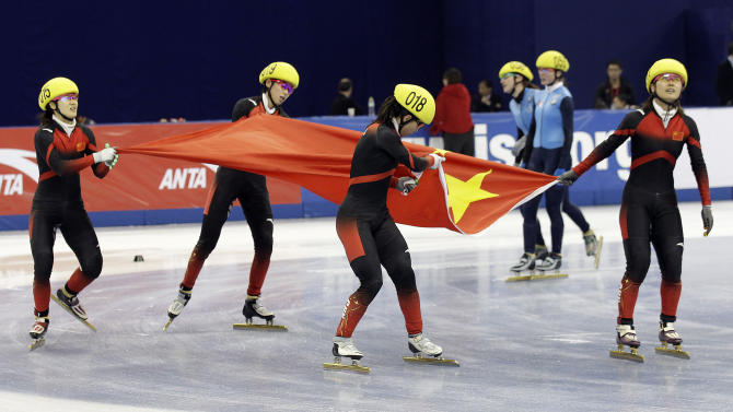Chinese team skaters celebrate with a Chinese flag after winning the ladies' 3000-meter relay final race at the ISU World Cup short track speed skating competition at Oriental Sports Center in Shanghai, China, on Sunday, Dec. 11, 2011. China won the race in a time of 4:12.394 seconds. The United States won the second place and Japanwon the bronze medal. (AP Photo/Eugene Hoshiko)