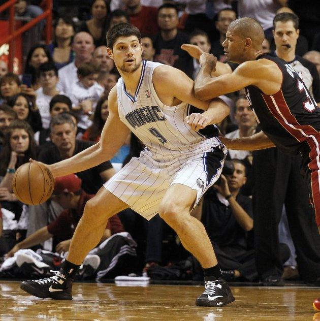 Orlando Magic center Vucevic is guarded by Miami Heat forward Battier during their NBA basketball game in Miami