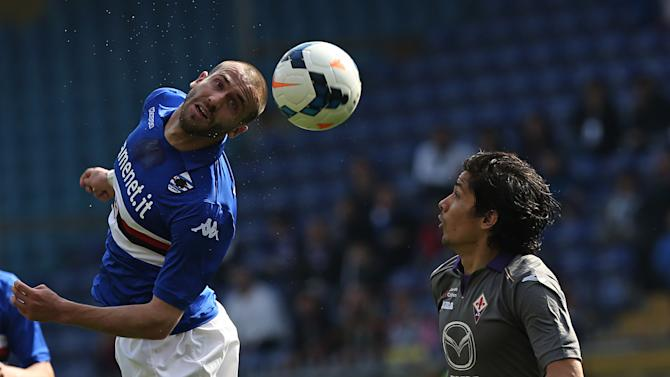 Sampdoria defender Lorenzo De Silvestri, left, heads the ball past Fiorentina midfielder Matias Ariel Fernandez during a Serie A soccer match, in Genoa, Italy, Sunday, March 30, 2014
